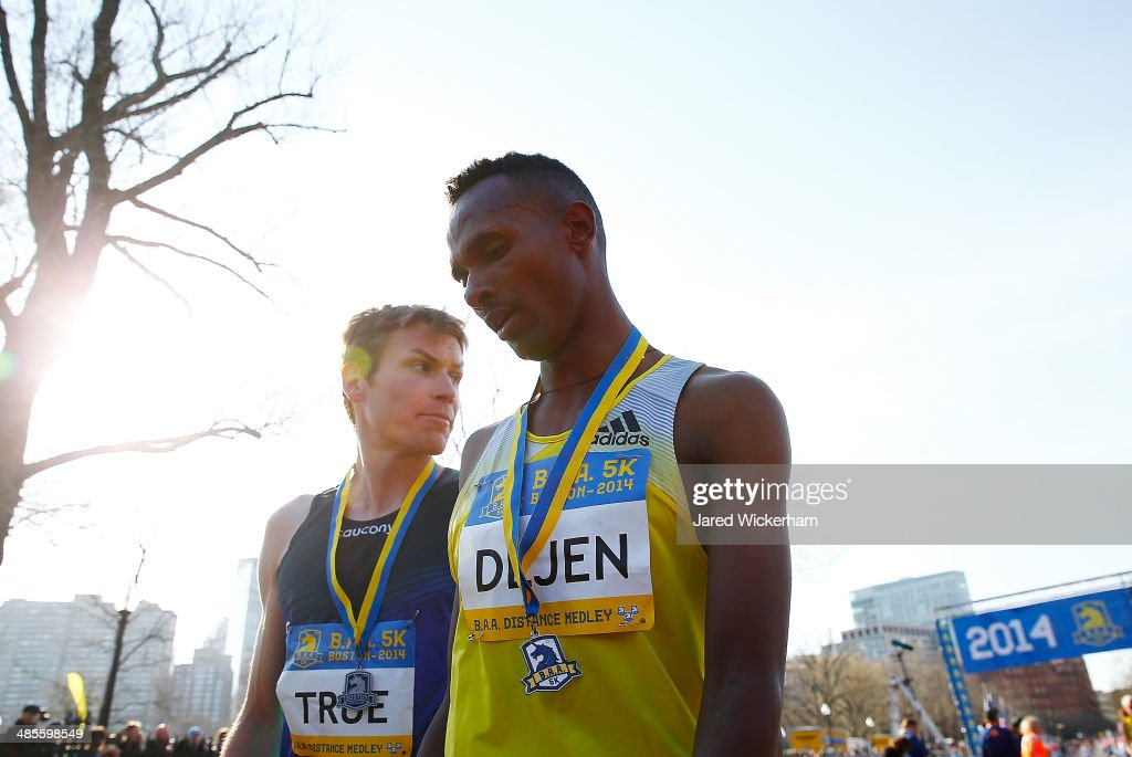 Dejan Gebremeskel of Ethopia (right) who edged out Ben True of the United States (left) for first place walk near the finish line of the 2014 B.A.A. 5K on April 19, 2014 in Boston, Massachusetts.