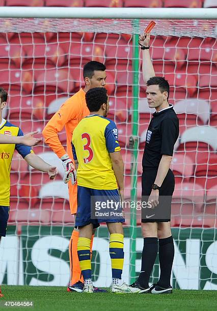 Dejan Iliev is shown the red card by Referee Shaun Hudson as Brandon OrmondeOttewill of Arsenal looks on during the match between Middlesbrough U21...