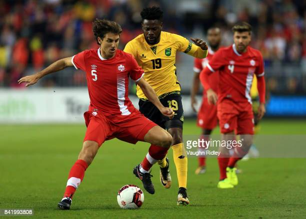 Dejan Jakovic of Canada battles for the ball with Ricardo Morris of Jamaica during the first half of an International Friendly match at BMO Field on...