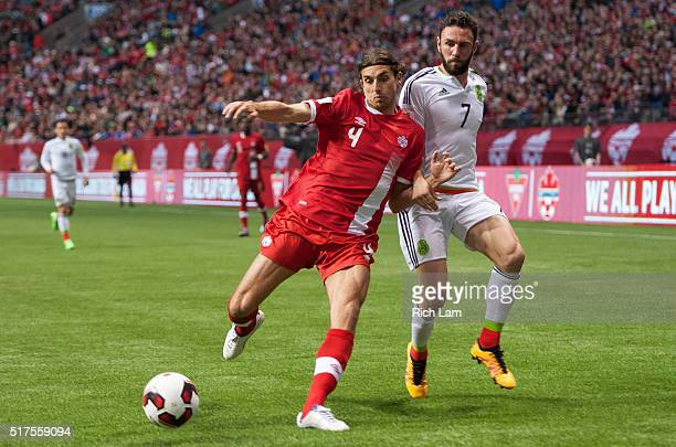 Dejan Jakovic of Canada battles Miguel Layun of Mexico for the ball during FIFA 2018 World Cup Qualifier soccer action at BC Place on March 25 2016...