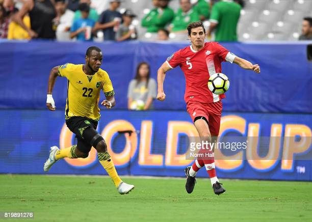 Dejan Jakovic of Canada brings the ball up field while being defended by Romario Williams of Jamaica during the first half in a quarterfinal match...