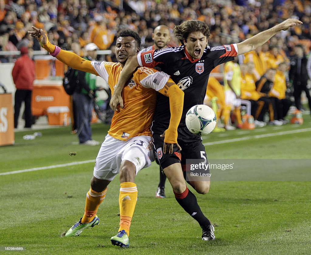 Dejan Jakovic #5 of the D.C. United grabs Giles Barnes #23 of the Houston Dynamo as they fight for possession of the ball during second half action at BBVA Compass Stadium on March 2, 2013 in Houston, Texas. Houston won 2-0.