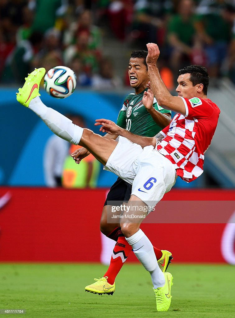 Dejan Lovren of Croatia and Giovani dos Santos of Mexico compete for the ball during the 2014 FIFA World Cup Brazil Group A match between Croatia and Mexico at Arena Pernambuco on June 23, 2014 in Recife, Brazil.