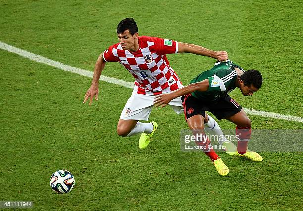 Dejan Lovren of Croatia fights off Giovani dos Santos of Mexico during the 2014 FIFA World Cup Brazil Group A match between Croatia and Mexico at...