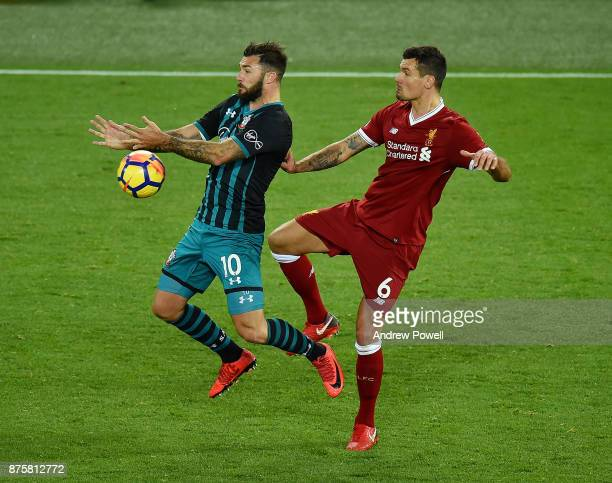 Dejan Lovren of Liverpool competes with Charlie Austin of Southampton during the Premier League match between Liverpool and Southampton at Anfield on...