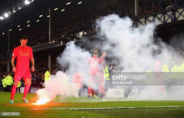 Dejan Lovren of Liverpool kicks a flare from the pitch as Sadio Mane of Liverpool scores their first goal during the Premier League match between...