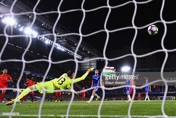 Dejan Lovren of Liverpool shootd past Thibaut Courtois of Chelsea as he scores their first goal during the Premier League match between Chelsea and...