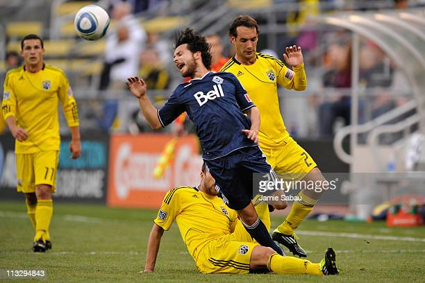 Dejan Rusmir of the Columbus Crew successfully tackles Davide Chiumiento of the Vancouver Whitecaps FC in the first half on April 30 2011 at Crew...