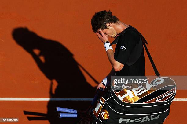 A dejected Andy Murray of Great Britain walks off court past Fernando Gonzalez of Chile following his defeat during the Men's Singles Quarter Final...