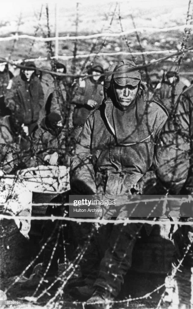 A dejected Argentinian prisoner sits behind barbed wire in a compound on the Falklands Islands during the war with British forces June 1982 Over 1200...
