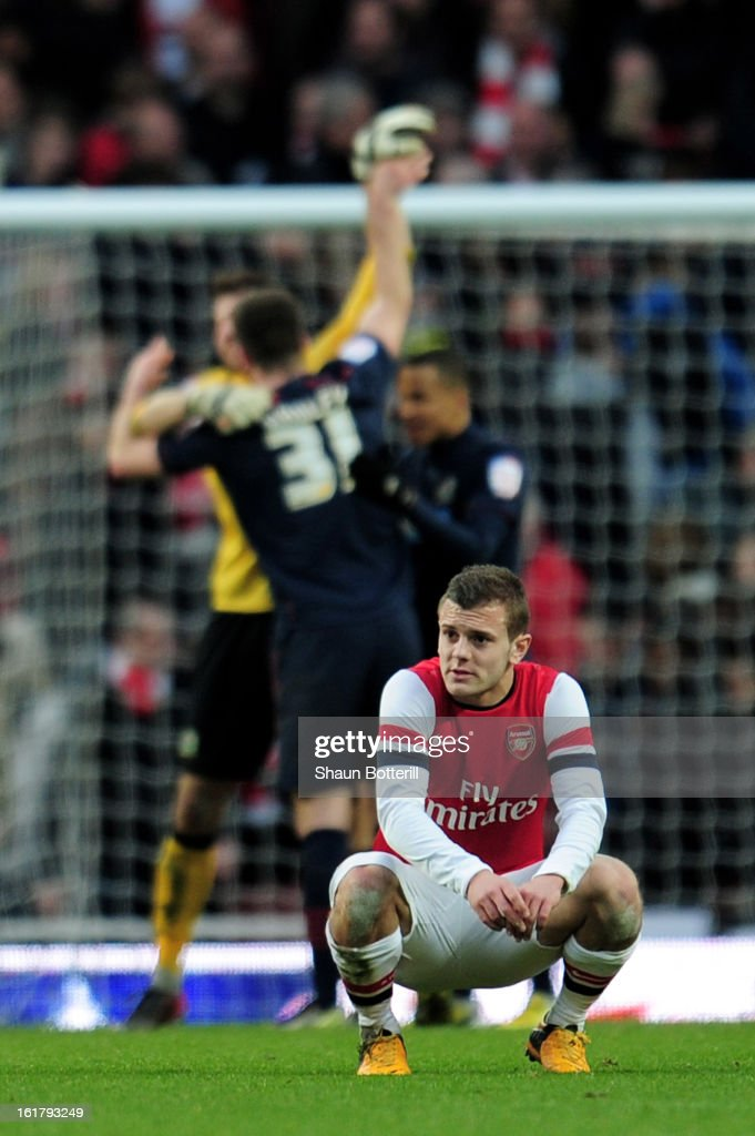 Dejected Arsenal player <a gi-track='captionPersonalityLinkClicked' href=/galleries/search?phrase=Jack+Wilshere&family=editorial&specificpeople=5446655 ng-click='$event.stopPropagation()'>Jack Wilshere</a> (R) looks on as Blackburn players celebrate their team's 1-0 victory during the FA Cup with Budweiser fifth round match between Arsenal and Blackburn Rovers at Emirates Stadium on February 16, 2013 in London, England.