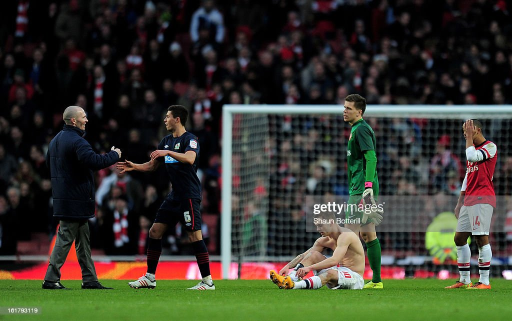 Dejected Arsenal players look on as Michael Appleton the Blackburn manager and Jason Lowe of Blackburn celebrate their team's 1-0 victory during the FA Cup with Budweiser fifth round match between Arsenal and Blackburn Rovers at Emirates Stadium on February 16, 2013 in London, England.