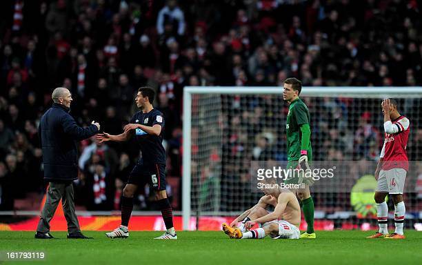 Dejected Arsenal players look on as Michael Appleton the Blackburn manager and Jason Lowe of Blackburn celebrate their team's 10 victory during the...