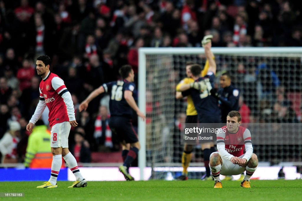 Dejected Arsenal players <a gi-track='captionPersonalityLinkClicked' href=/galleries/search?phrase=Mikel+Arteta&family=editorial&specificpeople=235322 ng-click='$event.stopPropagation()'>Mikel Arteta</a> (L) and <a gi-track='captionPersonalityLinkClicked' href=/galleries/search?phrase=Jack+Wilshere&family=editorial&specificpeople=5446655 ng-click='$event.stopPropagation()'>Jack Wilshere</a> (R) look on as Blackburn players celebrate their team's 1-0 victory during the FA Cup with Budweiser fifth round match between Arsenal and Blackburn Rovers at Emirates Stadium on February 16, 2013 in London, England.