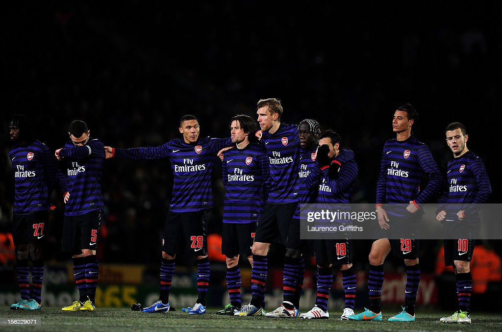 A dejected Arsenal team look on as they head out of the competition in the penalty shootout during the Capital One Cup quarter final match between Bradford City and Arsenal at the Coral Windows Stadium, Valley Parade on December 11, 2012 in Bradford, England.