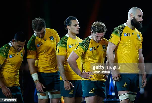 Dejected Australia players line up to collect their medals follwoing defeat in the 2015 Rugby World Cup Final match between New Zealand and Australia...