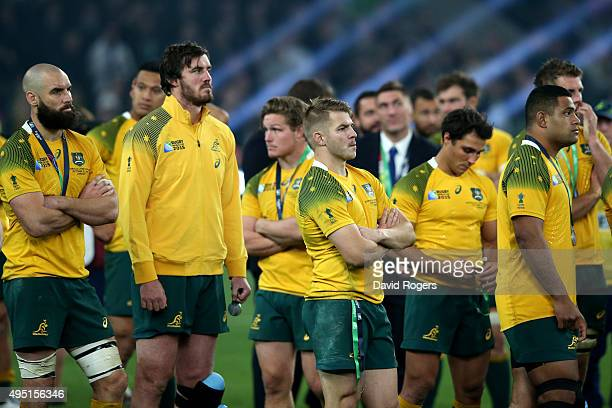 Dejected Australia players wait to collect their medals following the 2015 Rugby World Cup Final match between New Zealand and Australia at...