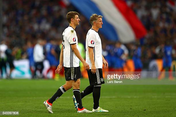 Dejected Bastian Schweinsteiger and Thomas Mueller of Germany leave the pitch after the defeat in the UEFA EURO semi final match between Germany and...