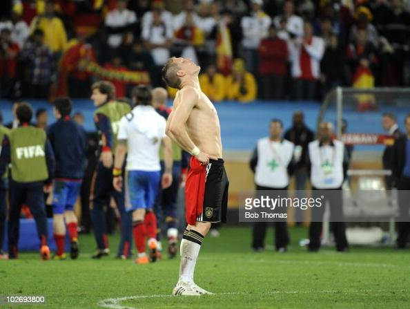 A dejected Bastian Schweinsteiger of Germany looks upwards after defeat in the 2010 FIFA World Cup South Africa Semi Final match between Germany and...