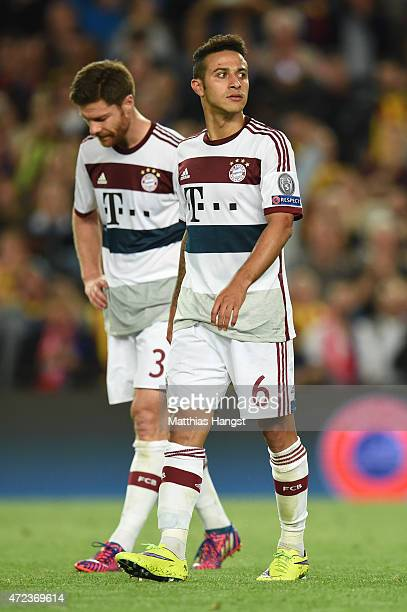 Dejected Bayern Muenchen teammates Xabi Alonso and Thiago walk off the pitch following their team's 30 defeat during the UEFA Champions League Semi...