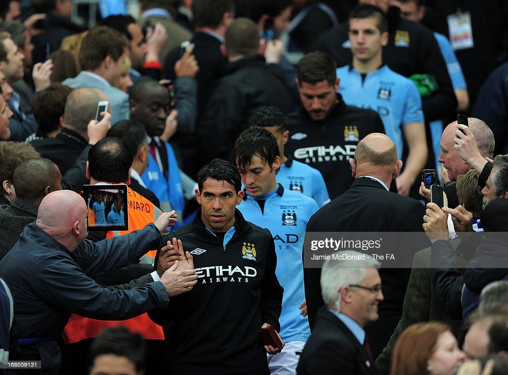 Dejected Carlos Tevez of Manchester City with teammates after defeat in the FA Cup with Budweiser Final match between Manchester City and Wigan Athletic at Wembley Stadium on May 11, 2013 in London, England.