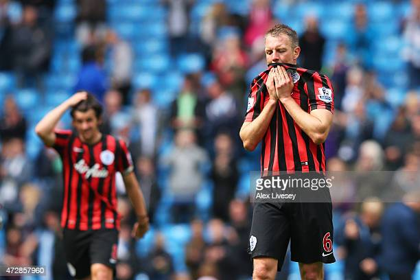 A dejected Clint Hill and Joey Barton of QPR react following their team's relegation during the Barclays Premier League match between Manchester City...