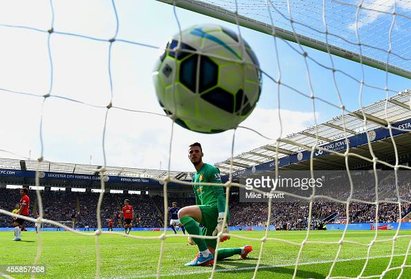 A dejected David De Gea of Manchester United looks at the ball in his net as Leonardo Ulloa of Leicester City scores his team's opening goal during...
