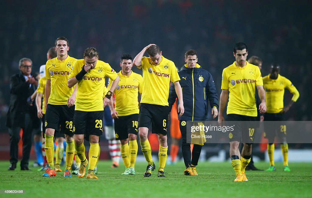 Dejected Dortmund players walk off the pitch following their team's 20 defeat during the UEFA Champions League Group D match between Arsenal and...