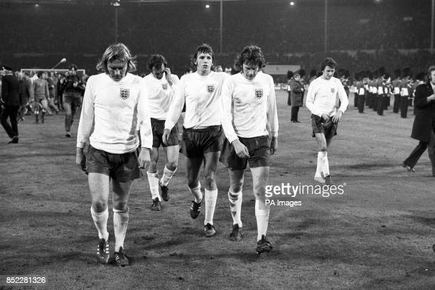 Dejected England players Tony Currie Paul Madeley Martin Peters and Mike Channon leave the pitch after a crucial World Cup qualifying match against...