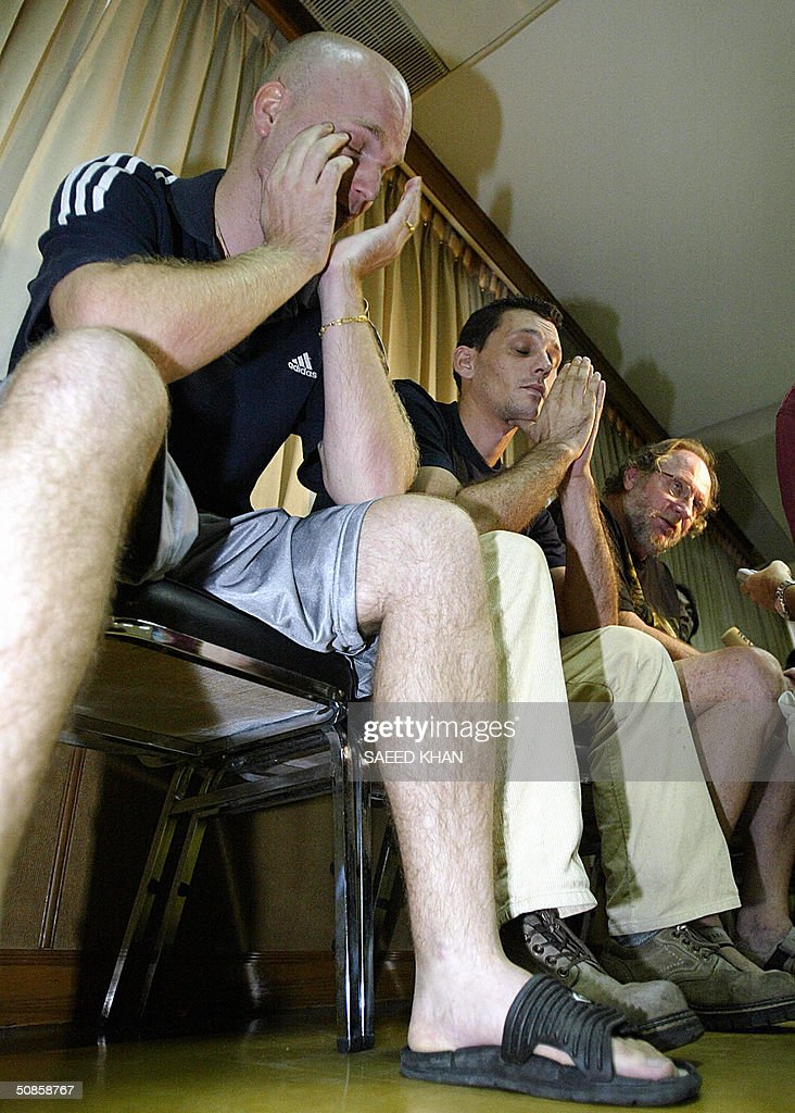 Dejected foreigners, British national Robert John Pope (R), German Schneider Uwe (C) and Hofer Philipp of South Africa, sit in police custody at an immigration department in Bangkok, 20 May 2004. Two Europeans and a South African have been arrested in the Thai capital for allegedly forging hundreds of Italian passports and visa seals they planned to sell in Europe. AFP PHOTO/ Saeed KHAN