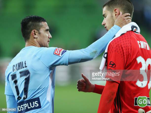 A dejected Goalkeeper Keegan Smith of Wellington Phoenix receives encouragement from Tim Cahill of the City after defeat during the round three...
