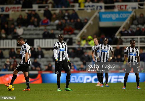 A dejected Hatem Ben Arfa Papiss Demba Cisse and Vurnon Anita of Newcastle United look on after the fourth goal during the Barclays Premier League...