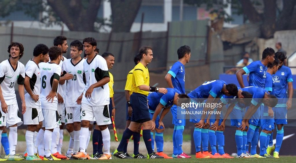 Dejected Indian footballers (R, in blue) gesture as Pakistani footballers (L) celebrate their two-goal victory against India during their second friendly football match in Bangalore at the Karnataka State Football Association Stadium in Bangalore on August 20, 2014. Pakistan pulled off a surprise 2-0 win over India, with a late goal from Saddam Hussain ensuring a share of the spoils for the visitors in the first football series between the arch rivals for a decade. AFP PHOTO/Manjunath KIRAN