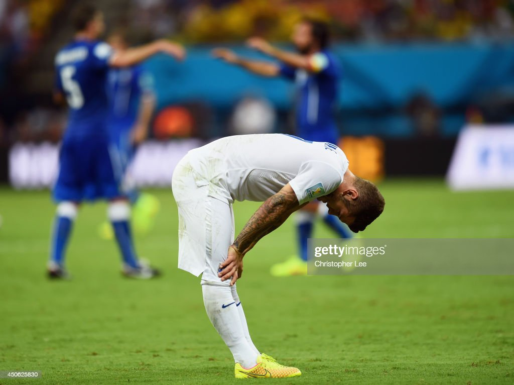 A dejected <a gi-track='captionPersonalityLinkClicked' href=/galleries/search?phrase=Jack+Wilshere&family=editorial&specificpeople=5446655 ng-click='$event.stopPropagation()'>Jack Wilshere</a> of England looks down as Italy celebrate defeating England 2-1 during the 2014 FIFA World Cup Brazil Group D match between England and Italy at Arena Amazonia on June 14, 2014 in Manaus, Brazil.