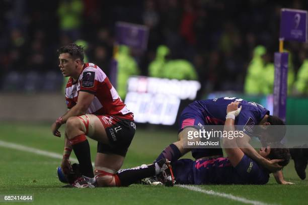 A dejected Lewis Ludlow of Gloucester reacts as Stade Francais players celebrate their 2517 victory during the European Rugby Challenge Cup Final...