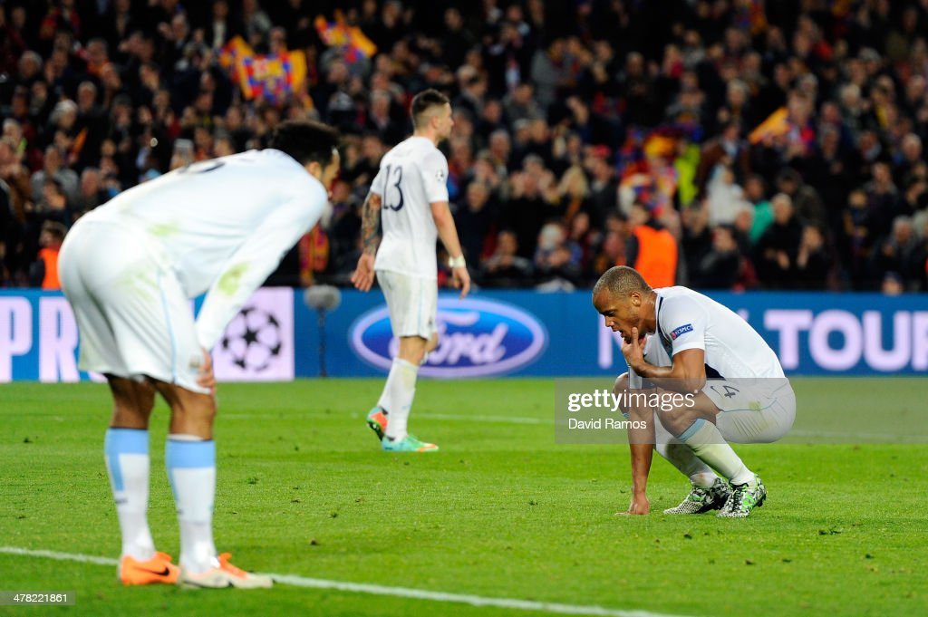 A dejected Manchester City captain <a gi-track='captionPersonalityLinkClicked' href=/galleries/search?phrase=Vincent+Kompany&family=editorial&specificpeople=504694 ng-click='$event.stopPropagation()'>Vincent Kompany</a> (R) reacts following his team's 2-1 defeat during the UEFA Champions League Round of 16, second leg match between FC Barcelona and Manchester City at Camp Nou on March 12, 2014 in Barcelona, Spain.