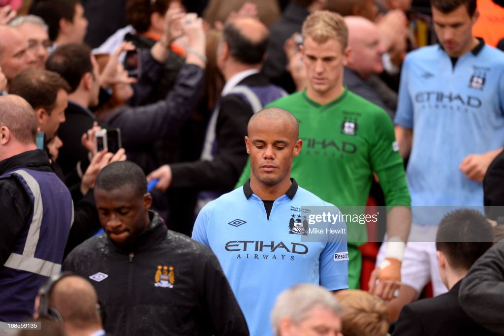 Dejected Manchester City players Yaya Toure, Vincent Kompany, Joe Hart, and Edin Dzeko walk down the steps after receiving their losers medals during the FA Cup with Budweiser Final between Manchester City and Wigan Athletic at Wembley Stadium on May 11, 2013 in London, England.