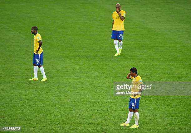 A dejected Paulinho of Brazil looks on with teammates Ramires and Maicon during the 2014 FIFA World Cup Brazil Semi Final match between Brazil and...