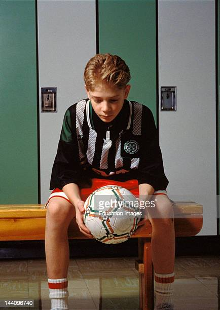 Dejected Player With Soccer Ball In Locker Room After A Loss