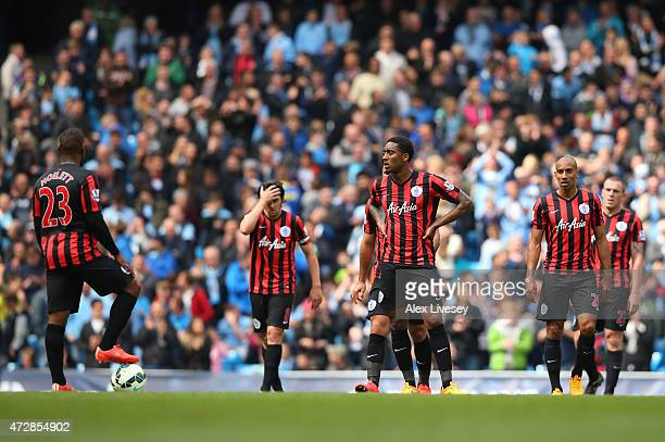 Dejected QPR players look on during the Barclays Premier League match between Manchester City and Queens Park Rangers at the Etihad Stadium on May 10...