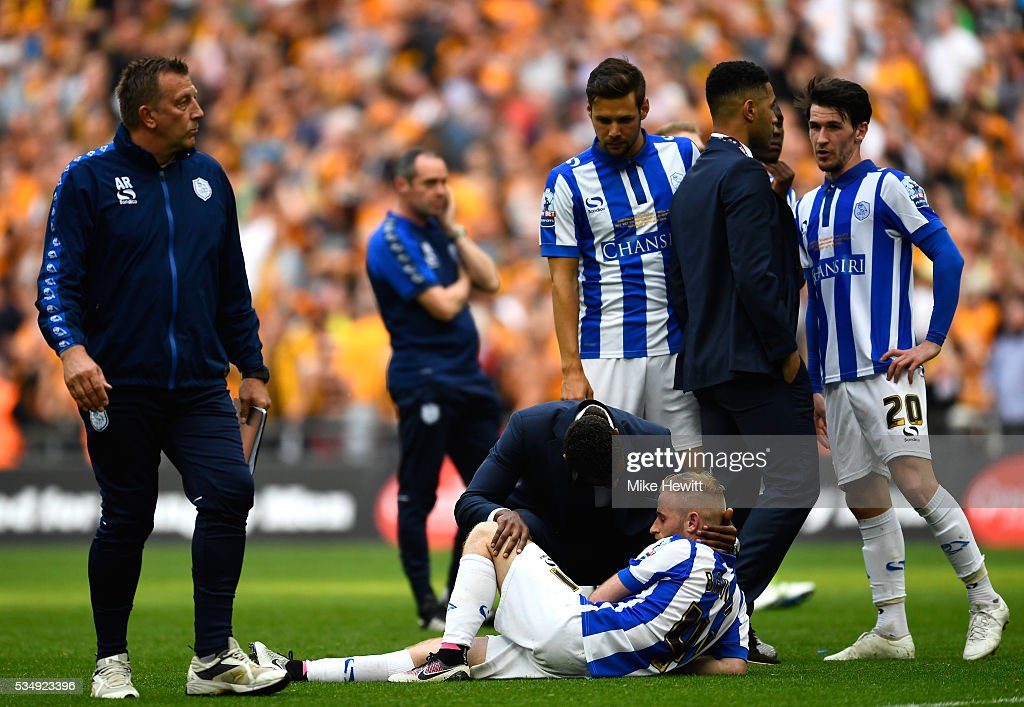 Dejected Sheffield Wednesday players are consoled after defeat in the Sky Bet Championship Play Off Final match between Hull City and Sheffield Wednesday at Wembley Stadium on May 28, 2016 in London, England.