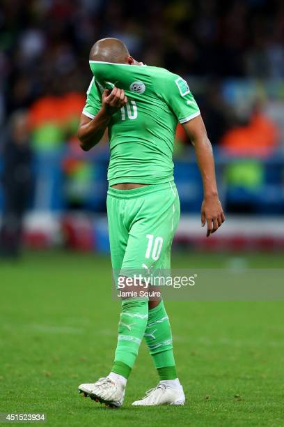 A dejected Sofiane Feghouli of Algeria wipes his face after being defeated by Germany 21 during the 2014 FIFA World Cup Brazil Round of 16 match...