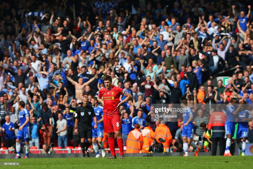 A dejected <a gi-track='captionPersonalityLinkClicked' href=/galleries/search?phrase=Steven+Gerrard&family=editorial&specificpeople=202052 ng-click='$event.stopPropagation()'>Steven Gerrard</a> of Liverpool looks on as the Chelsea fans celebrate after Willian of Chelsea scored their second goal during the Barclays Premier League match between Liverpool and Chelsea at Anfield on April 27, 2014 in Liverpool, England.