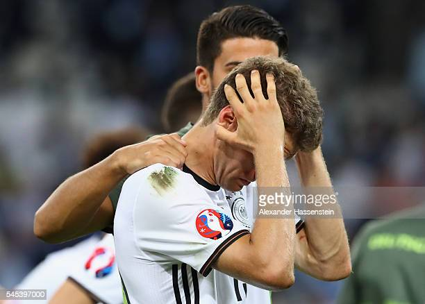 Dejected Thomas Mueller of Germany is consoled by Emre Can after defeat in the UEFA EURO semi final match between Germany and France at Stade...