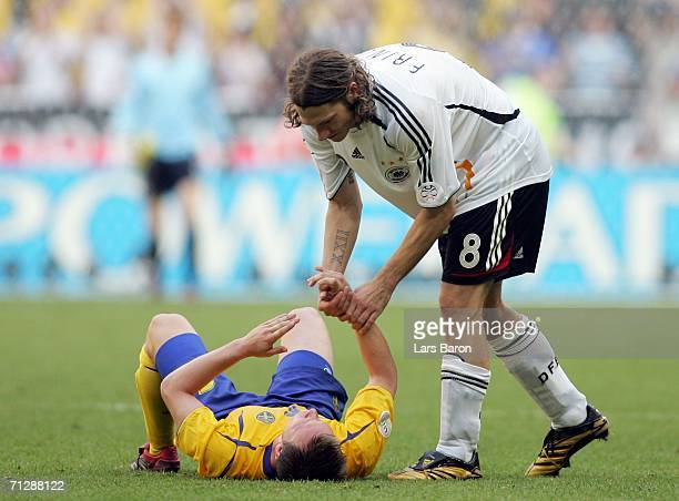 A dejected Tobias Linderoth of Sweden is helped to his feet by Torsten Frings of Germany during the FIFA World Cup Germany 2006 Round of 16 match...