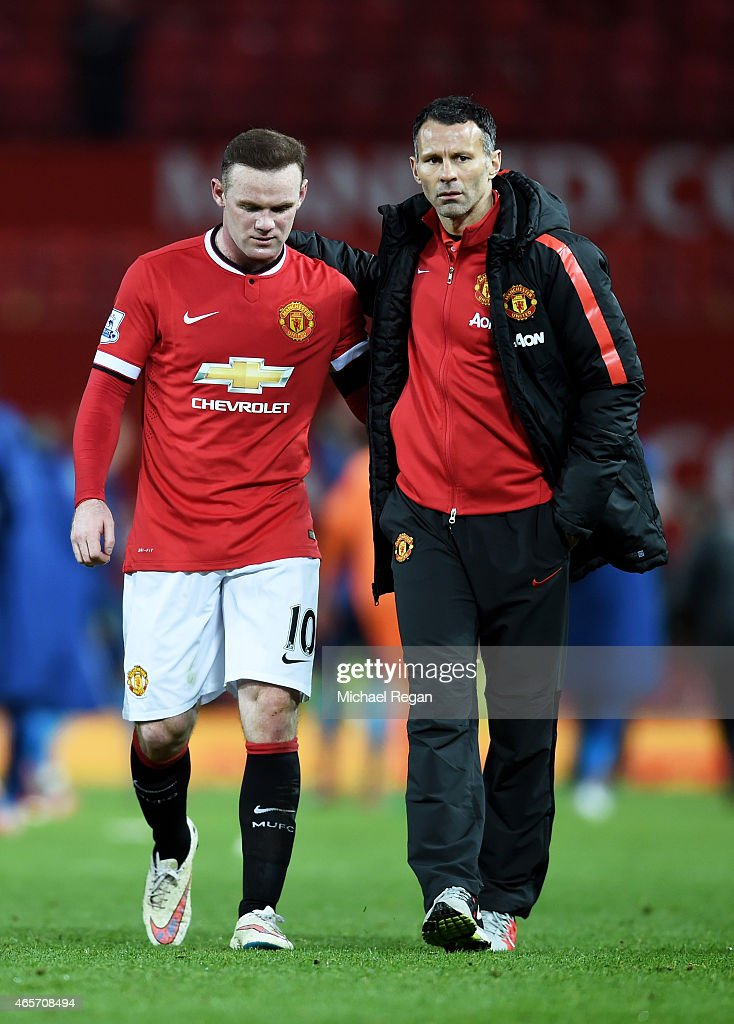 A dejected Wayne Rooney of Manchester United is consoled by Assistant Ryan Giggs of Manchester United following their team's 2-1 defeat during the FA Cup Quarter Final match between Manchester United and Arsenal at Old Trafford on March 9, 2015 in Manchester, England.