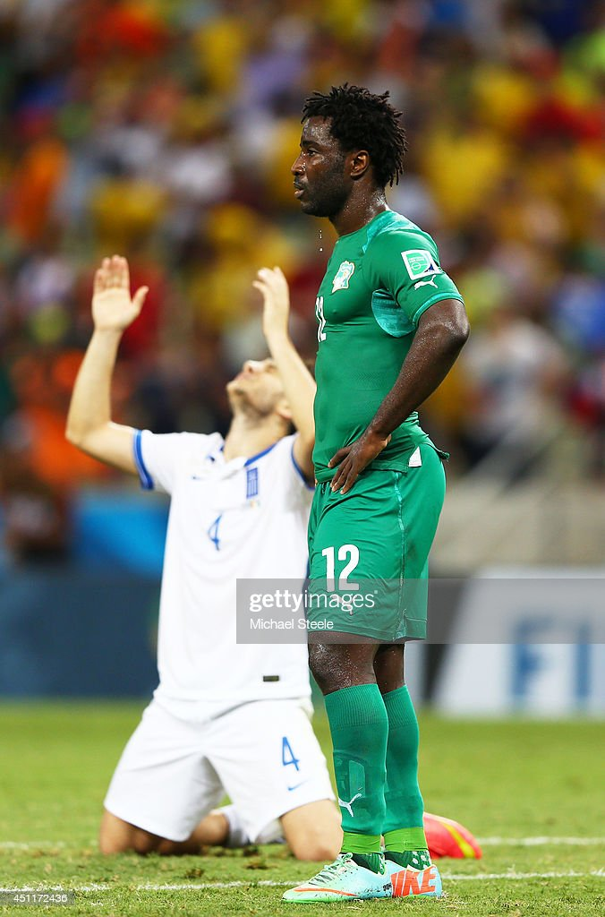 A dejected Wilfried Bony of the Ivory Coast looks on as Konstantinos Manolas of Greece celebrates during the 2014 FIFA World Cup Brazil Group C match...