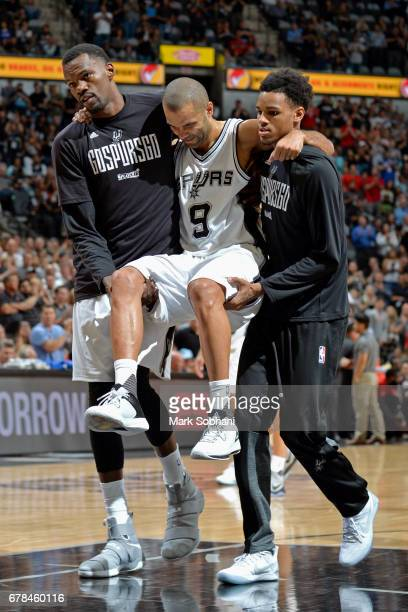 Dejounte Murray and Dewayne Dedmon carry Tony Parker of the San Antonio Spurs off the court after sustaining a knee injury during Game Two of the...