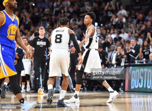 Dejounte Murray and Patty Mills of the San Antonio Spurs react to a play during Game Four of the Western Conference Finals of the 2017 NBA Playoffs...