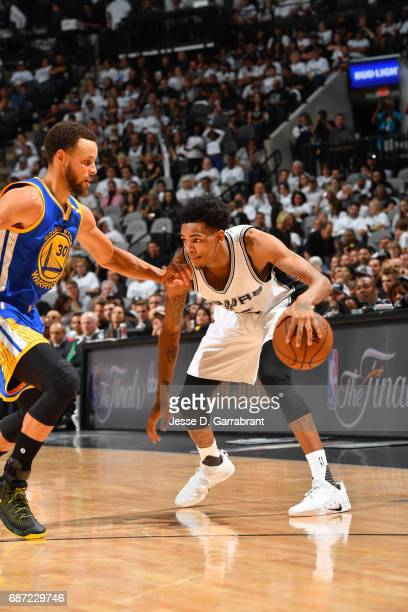 Dejounte Murray of the San Antonio Spurs dribbles the ball while defended by Stephen Curry of the Golden State Warriors in Game Three of the Western...